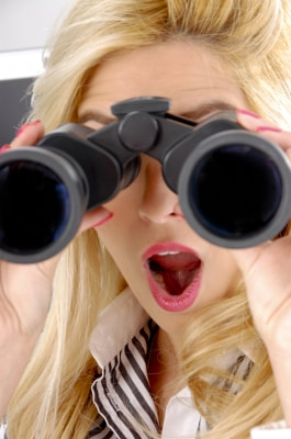 woman spying with binoculars